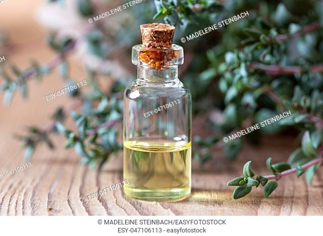A bottle of essential oil with fresh thyme in the background
