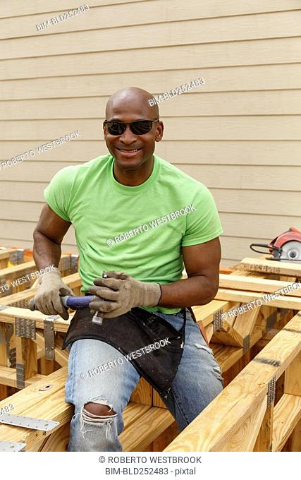 Black man posing with hammer at construction site
