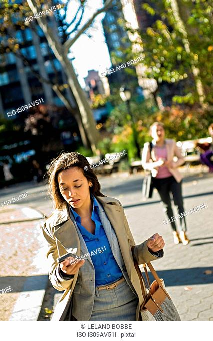 Young woman reading smartphone whilst walking through city park