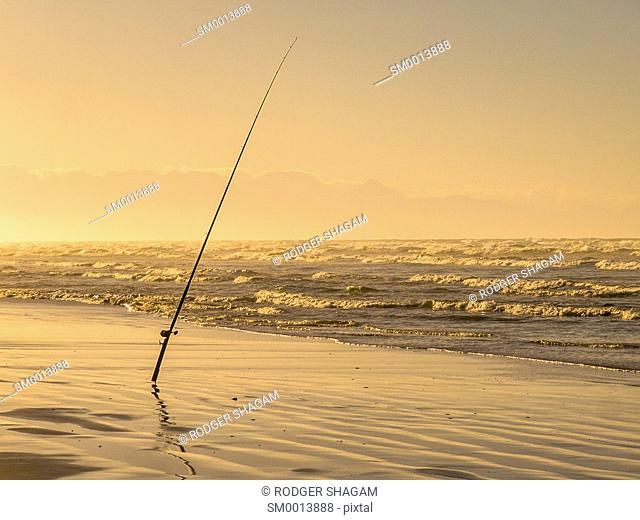 A fishing rod on a support stand - waiting for the bite. Sunrise on the beach. Cape Town, South Africa. .