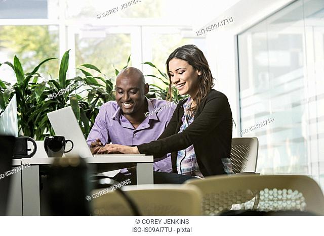 Male and female business colleagues using laptop in office