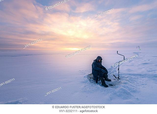 Fisherman in the frozen Baltic sea with snow in winter and sunset at St Petersburg, Russia