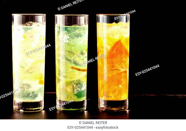 Three highball glasses filled with alcoholic or non-alcoholic cocktail drinks mixed with ice and tropical fresh fruits as lemon, lime and orange, on a table