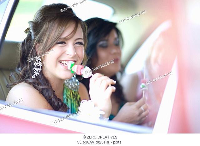Teenage girl in gown eating kebab