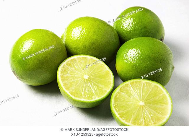 Limes and a Halved Lime on a White Background
