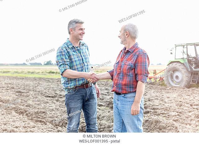 Two farmers on field shaking hands
