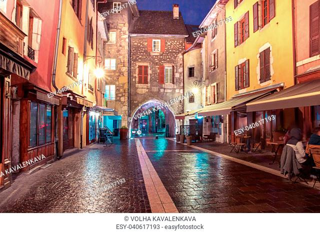 Gorgeous medieval arch gate Sepulchre Gate on the street Rue Sainte-Claire in Old Town at rainy night, Annecy, France