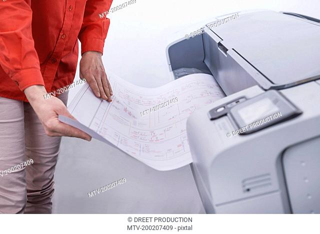 Woman using photocopier in office, Munich, Bavaria, Germany