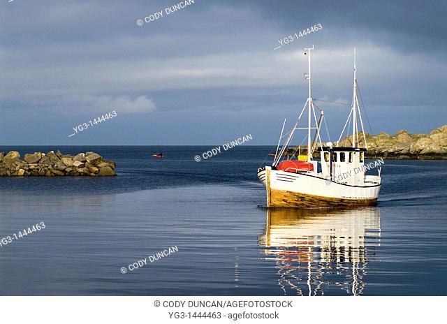 Small fishing boat arrives in harbor, Stamsund, Lofoten islands, Norway