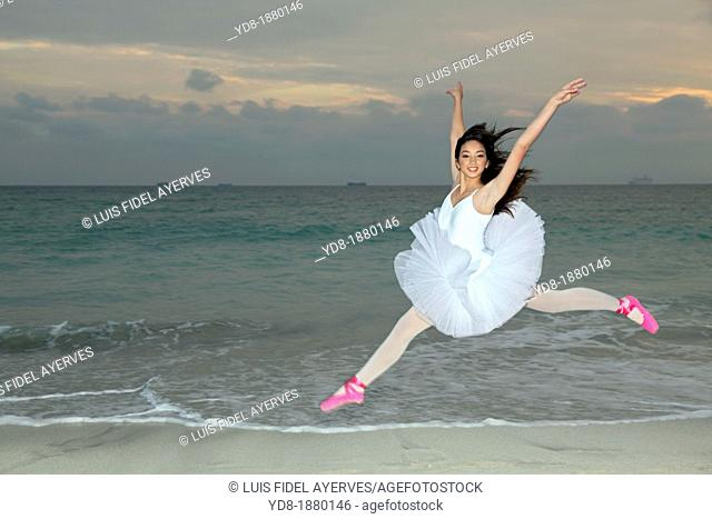 Young woman dancer jumping on the beach, Miami Beach, Florida, USA
