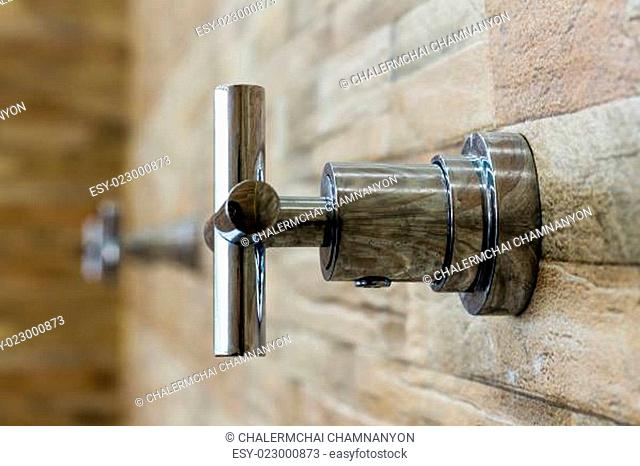 faucet on brick wall background