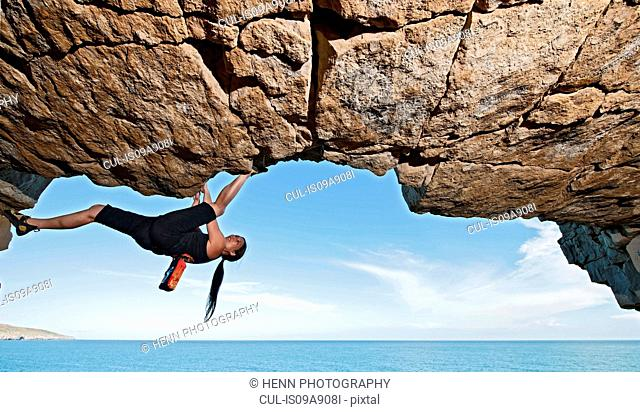 Mature woman rock climbing over ocean