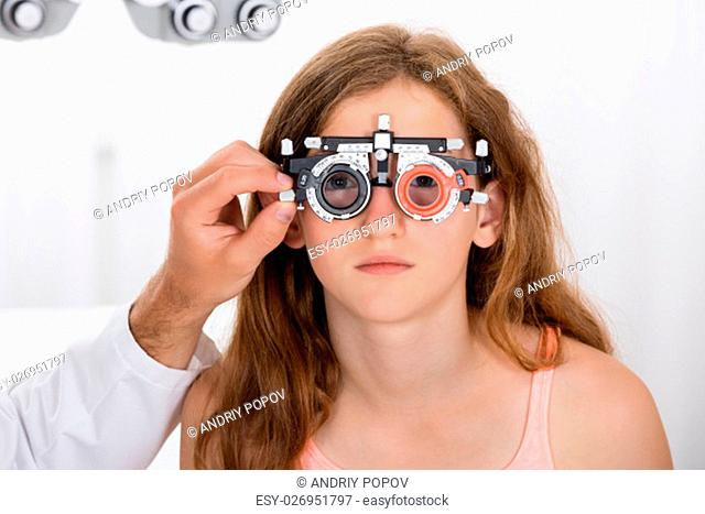 Close-up Of An Optometrist Checking Girl's Vision With Trial Frame At Eye Clinic