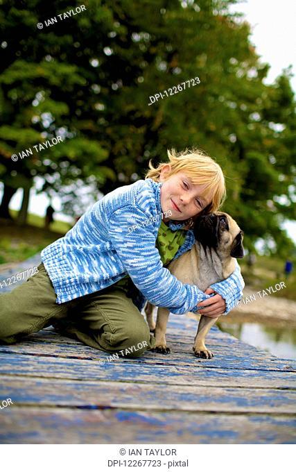 Girl hugging a dog on a dock; Picton, Ontario, Canada