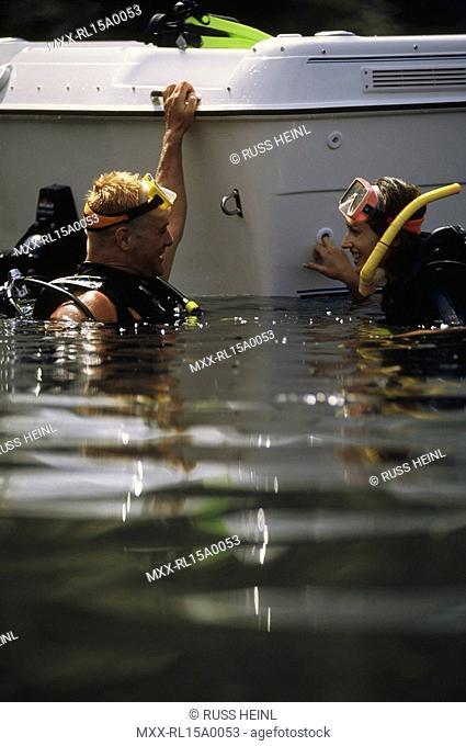 scuba divers talking beside boat