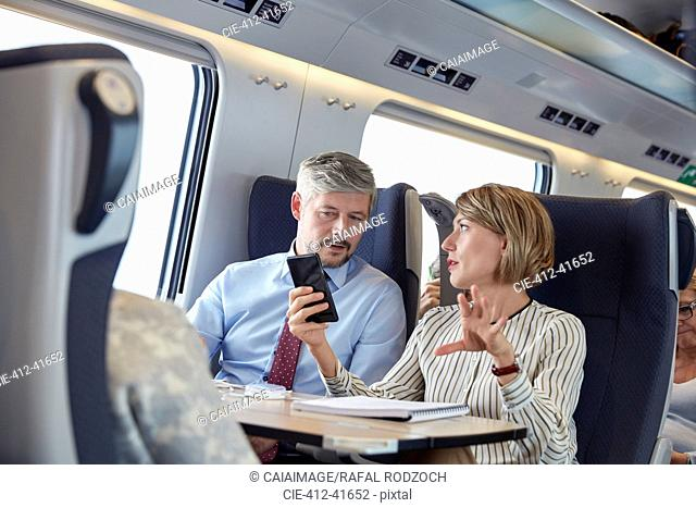 Business people working, using smart phone and talking on passenger train