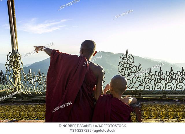 Myanmar (formerly Burma). Kyaiktiyo. State Mon. Sacred site of the golden rock. Monk and novice