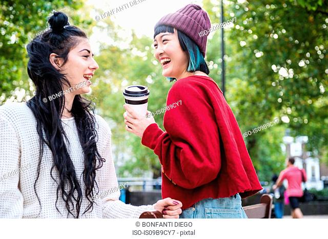 Two young stylish women laughing in city park