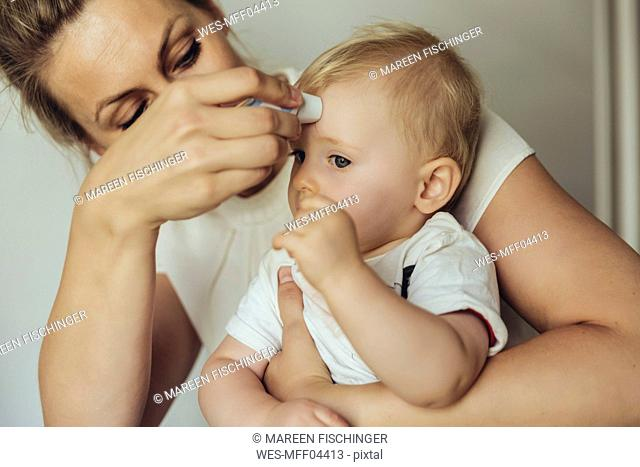 Mother using a skin thermometer to take babyƒ.s temperature