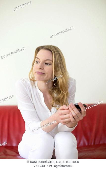 Portrait of a pretty pensive woman with mobile on the couch