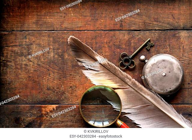 Magnifying glass near pocket watch and feather on wooden background