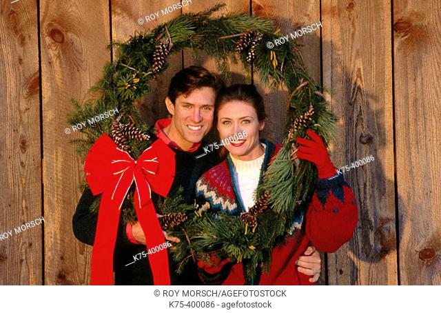 Couple holding Christmas wreath for portrait