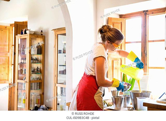 Young woman pouring liquid lavender soap into bowl in handmade soap workshop