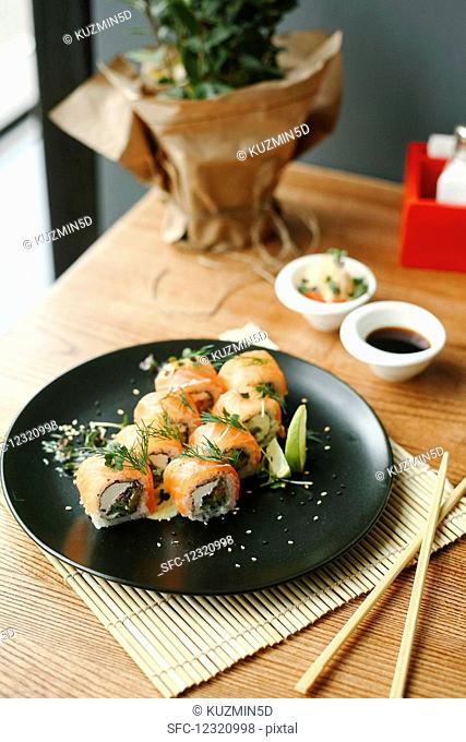 Sushi rolls with salmon, fresh cheese and herbs on a black plate