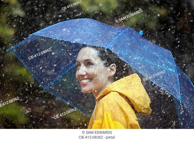 Happy woman with umbrella in rain