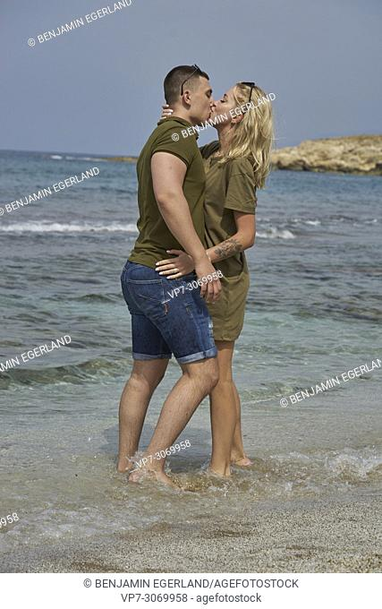 Happy young couple kissing on the beach, Russian ethnicity, Hersonissos, Crete, Greece