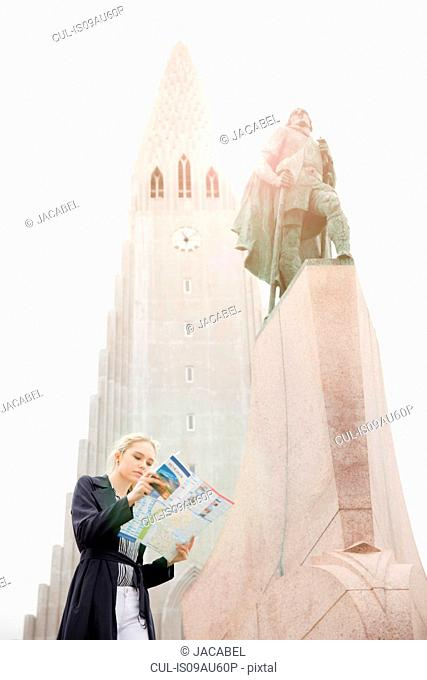 Low angle view of teenage girl looking at map next to statue, Hallgrímskirkja, Reykjavik, Iceland