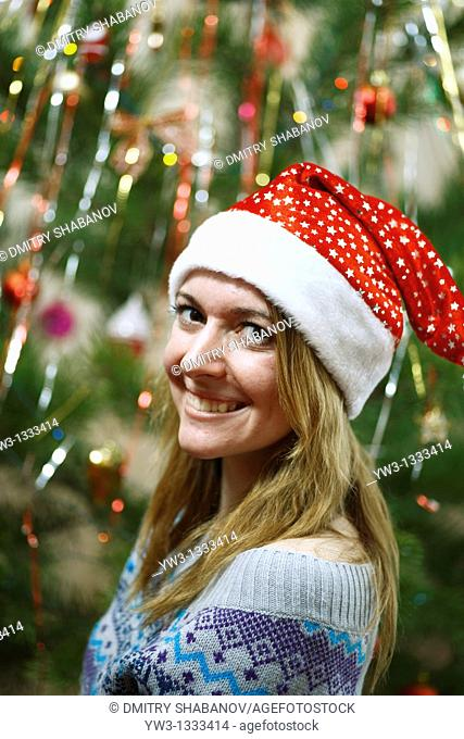 closeup of pretty girl in christmas hat against decorated xmas tree