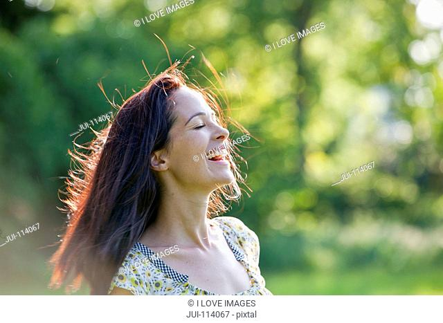 Carefree happy brunette woman in sunny summer park