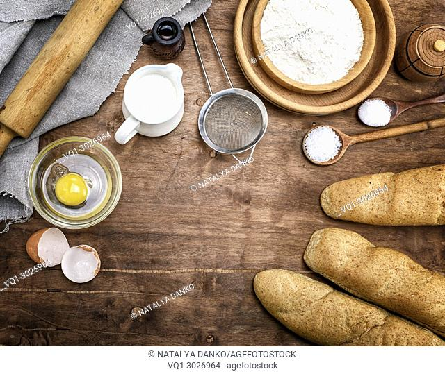 white wheat flour in a wooden bowl and baked baguettes on a brown wooden background, top view, empty space in the middle