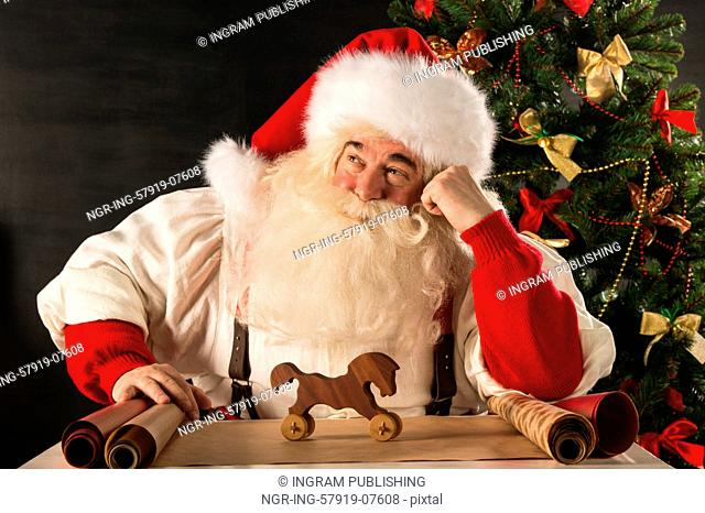 Santa Claus working - preparing and wrapping christmas gifts, toys before sending it to children