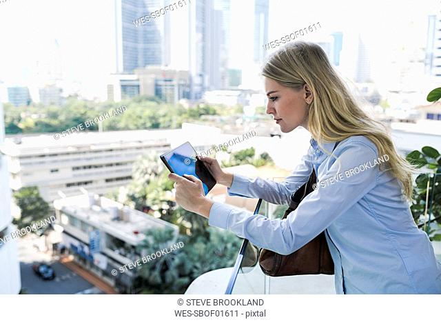Blond woman with tablet leaning agianst glass railing in the city