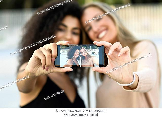 Two friends taking selfie with cell phone, close-up