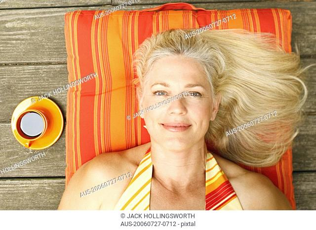 Portrait of a mature woman lying on her back and smiling