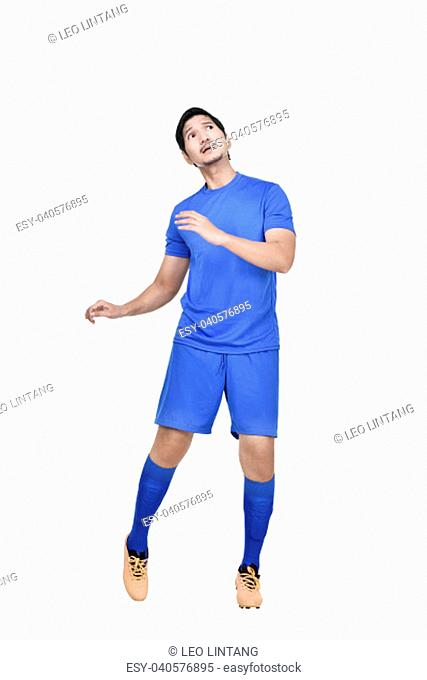 Attractive asian male soccer player heading the ball isolated over white background