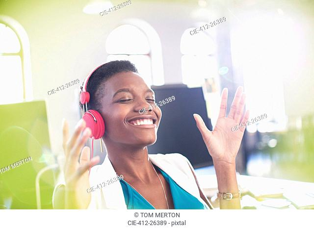 Smiling businesswoman listening to music on headphones in office with eyes closed