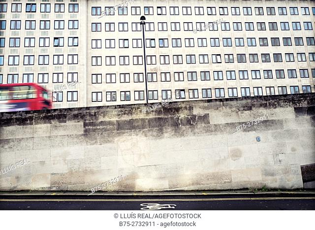 Concrete wall with a building in the background with many windows and a red bus in motion. Shell Centre, Waterloo, London, England