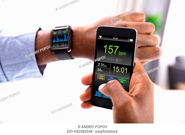 Close-up Of A Man's Hand With Smartwatch And Cellphone Showing Heartbeat Rate