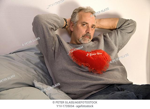Middle-age man holding a heart-shaped pillow with 'I Love You' written on it