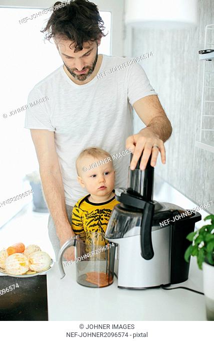 Father with baby son making orange juice