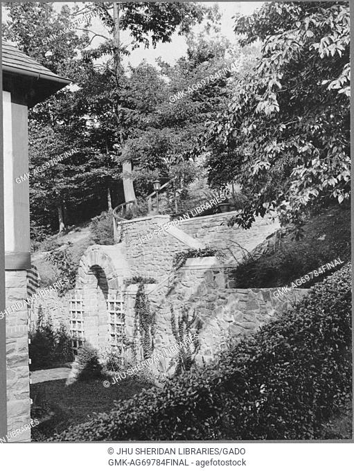 Foliage and ivy growing around and upon stonework construction behind house, with trees in the vicinity; Roland Park/Guilford, 1910