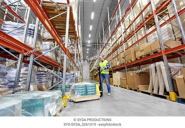 male worker with loader working at warehouse