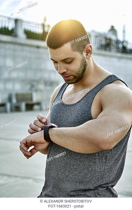 Male athlete using smart watch while standing at footpath