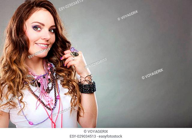 Happy pretty young woman wearing many plenty of jewelry necklaces beads, rings and bracelets. Portrait of gorgeous fashion girl in studio on gray
