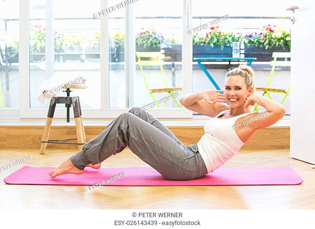 blond woman doing yoga in her living room