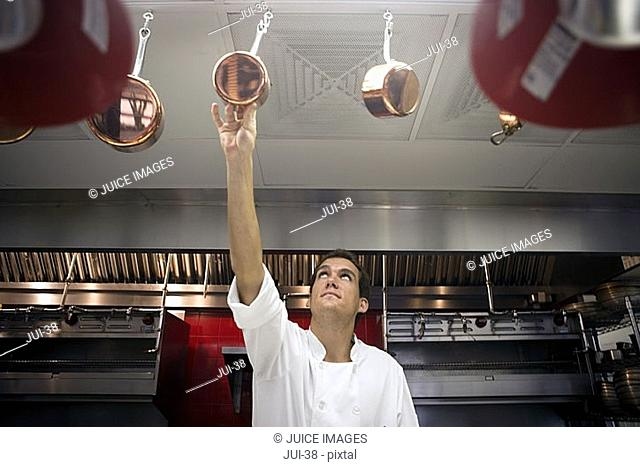 Chef reaching for pan in commercial kitchen